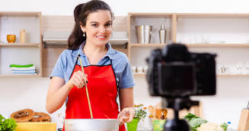 Lady cooking in the kitched recording video using her phone